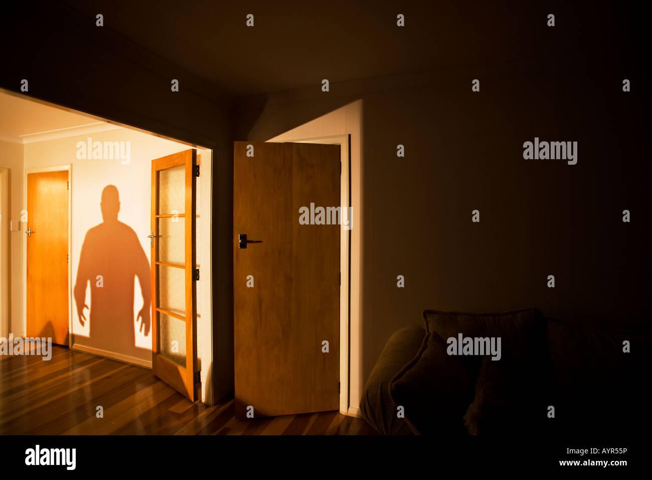 Ombre de l'homme sur le mur à côté d'une pièce sombre, Photo Stock