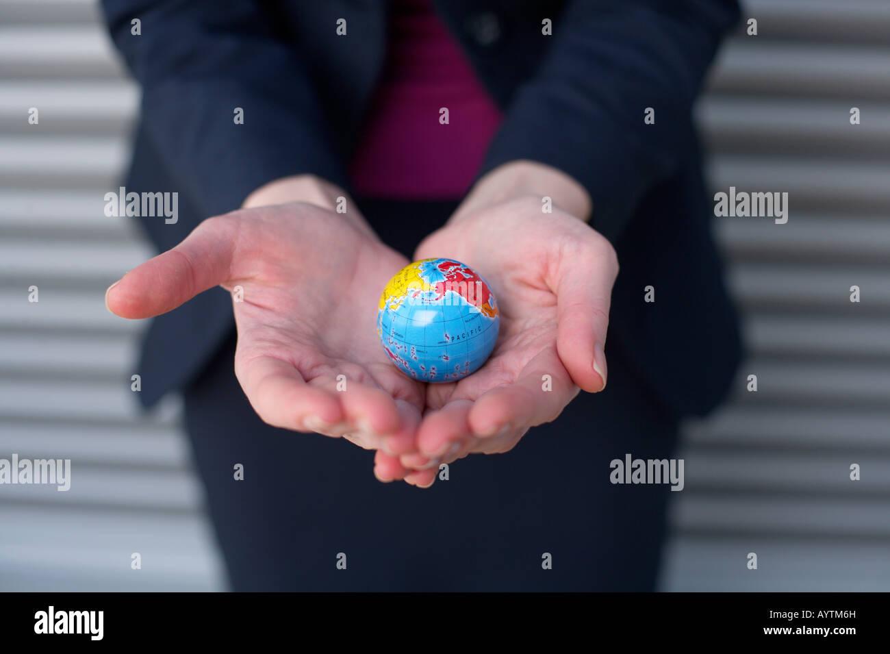Businesswoman holding a globe mini sur les mains Photo Stock
