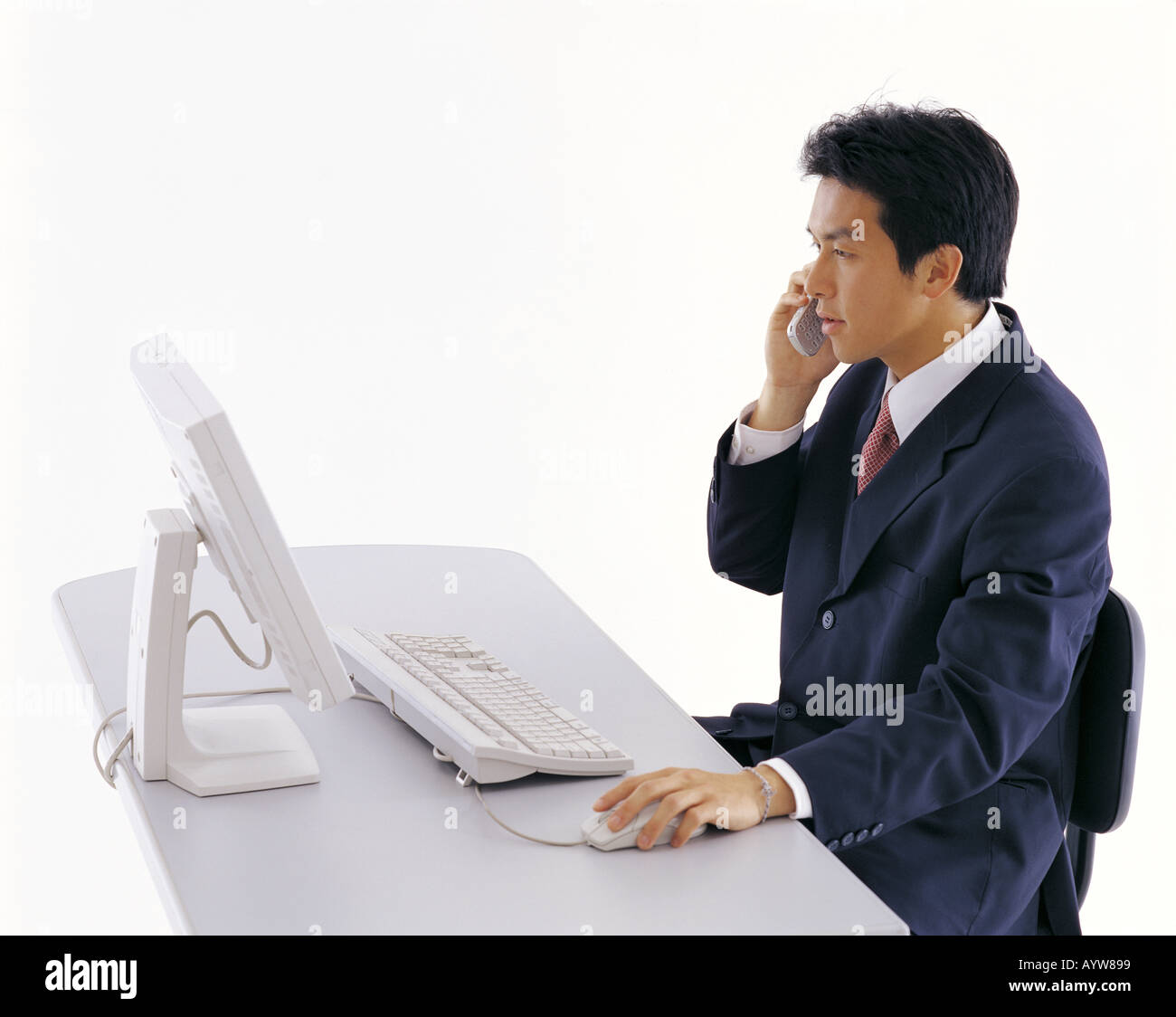 Office worker talking on a cell phone in front of computer Banque D'Images