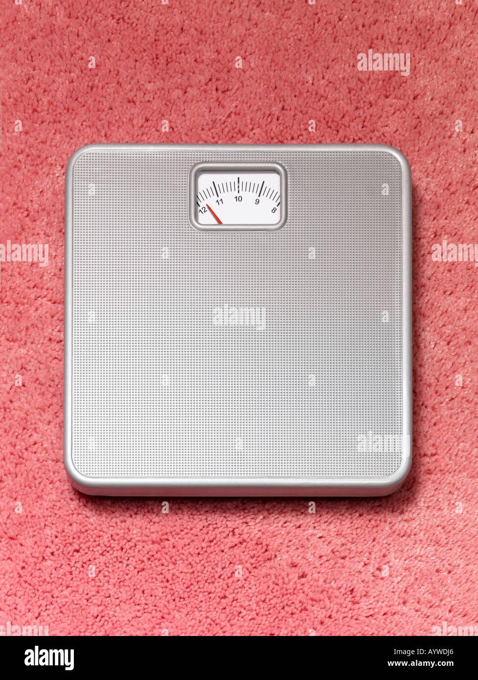 Une salle de bains pourvue d''une balance sur un tapis moelleux rose Photo Stock