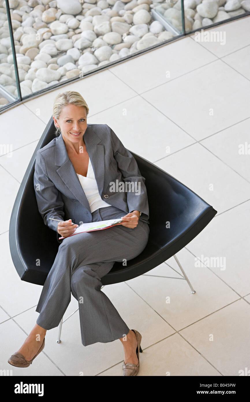Femme d'affaires et un élégant fauteuil Photo Stock