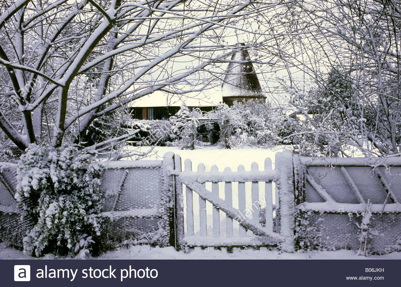 Les maisons Oast Hampshire vue par grille du jardin en hiver neige ...