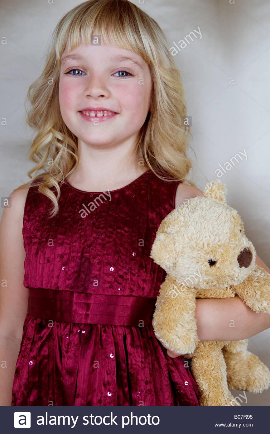 Jeune fille en robe de soirée, holding a teddy bear Photo Stock