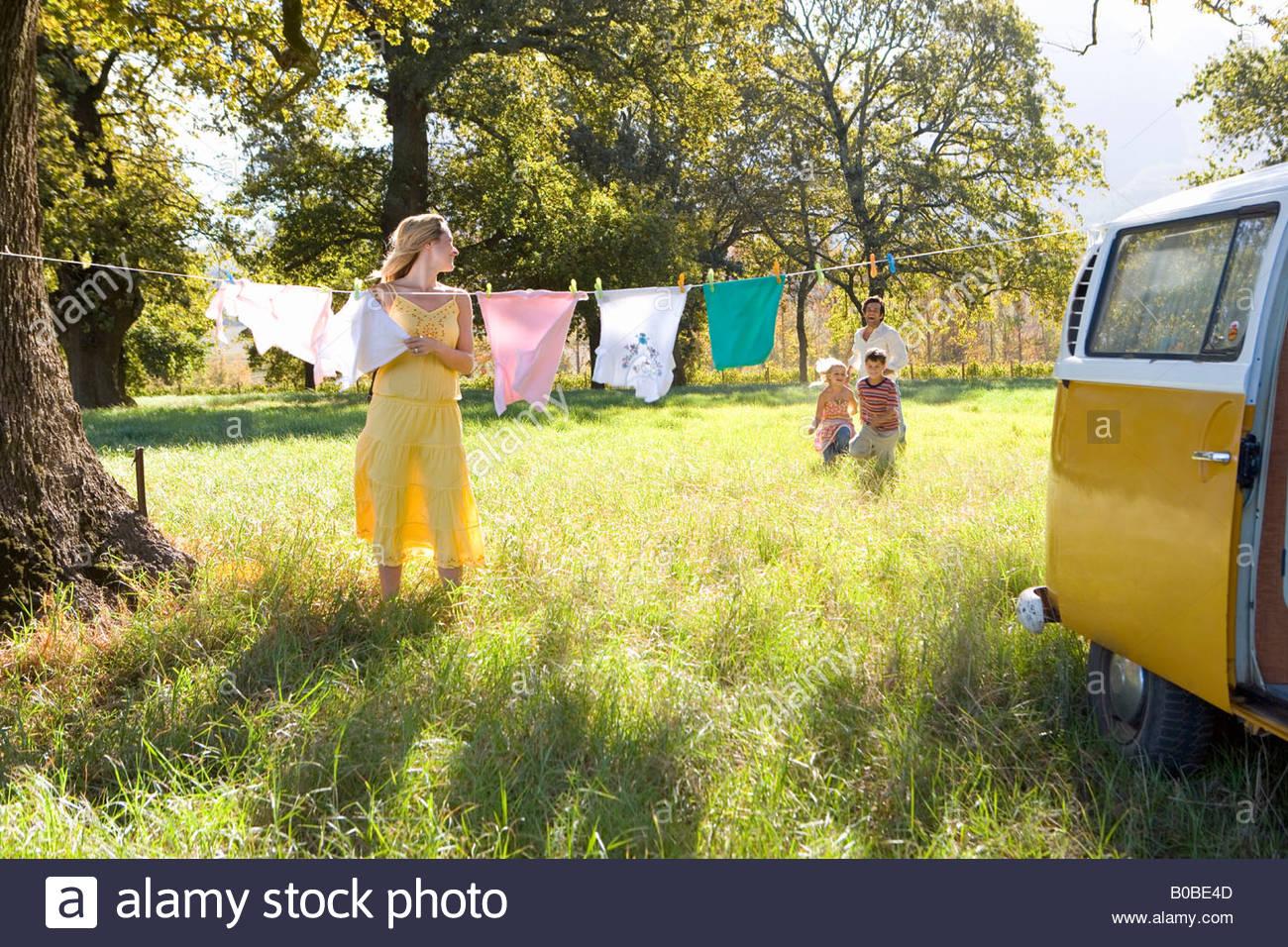 Jeune femme accroché à la ligne de lavage par le camping-car, en revenant sur le terrain de la famille Photo Stock