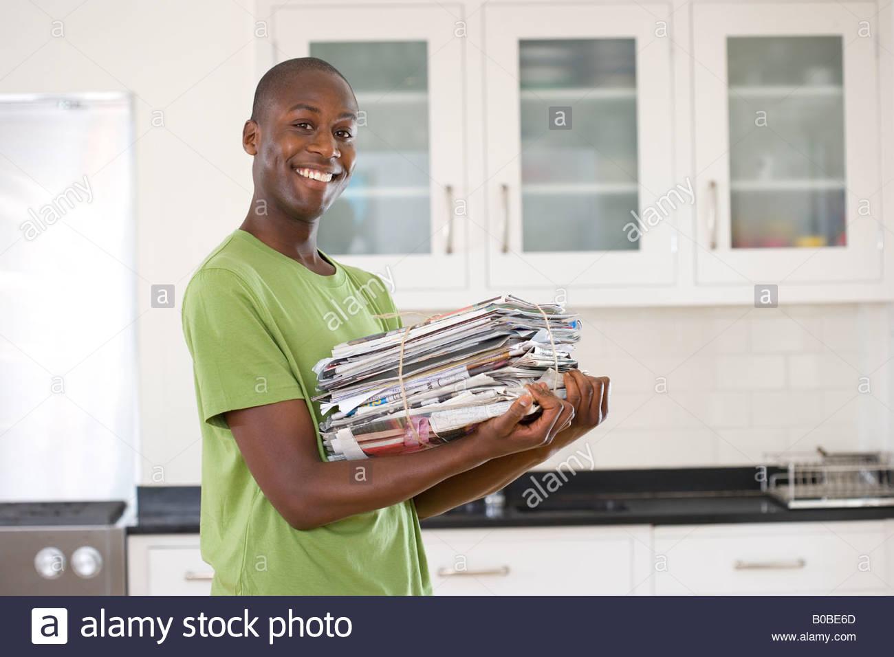 Jeune homme avec l'ensemble de journaux dans la cuisine, smiling, portrait Banque D'Images