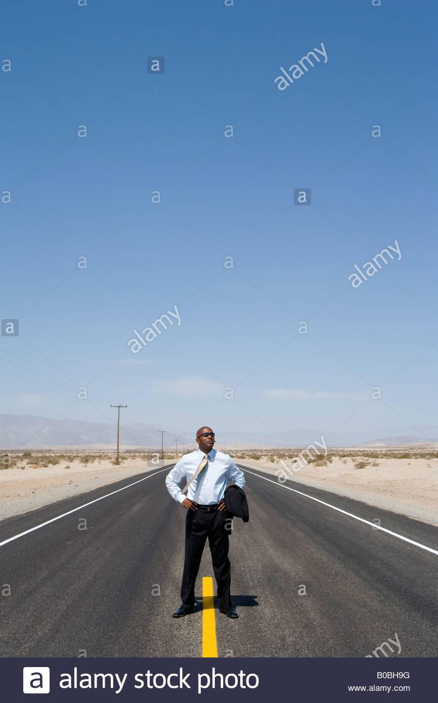 Homme d'affaires en ligne en milieu de route dans le désert avec les mains sur les hanches Photo Stock