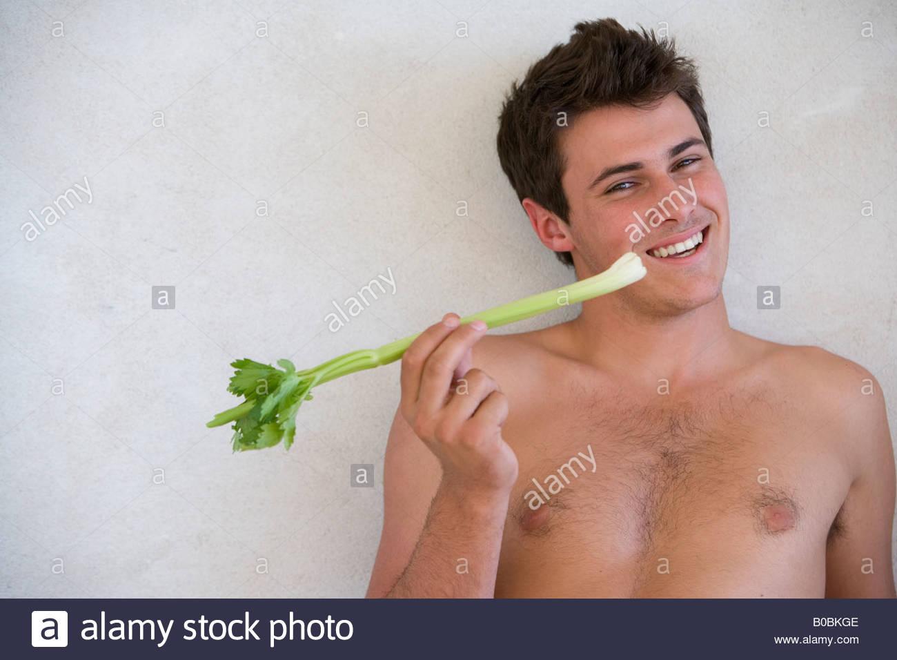 Jeune homme torse nu avec céleri, smiling, portrait Photo Stock