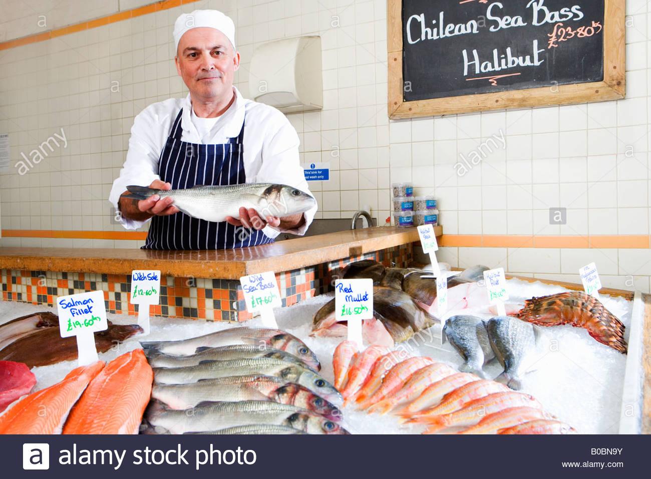 Poissonnier derrière compteur dans boutique, tenant des poissons, portrait Photo Stock