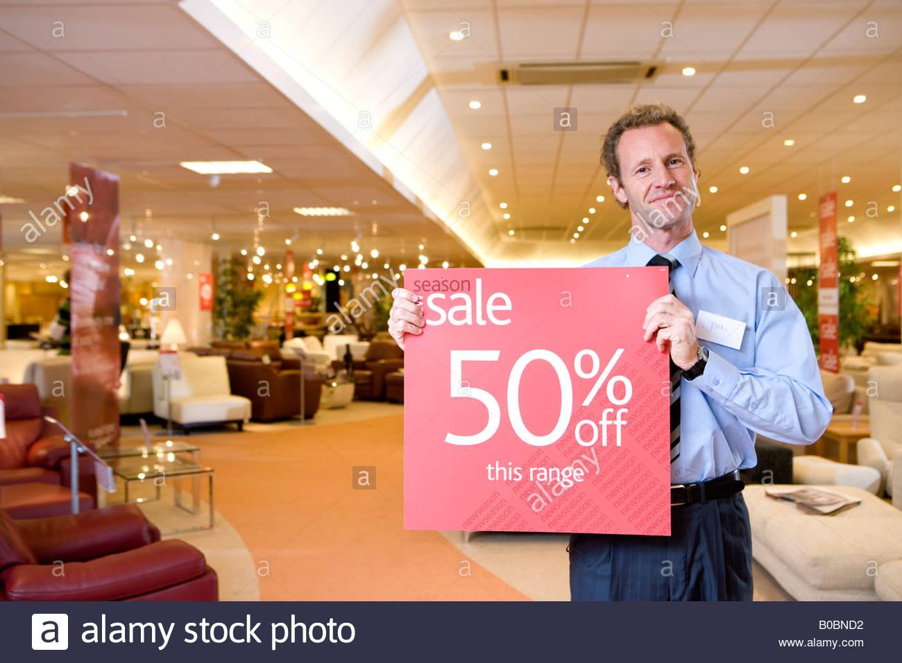 Vendeur avec 'sale' ouvrir une boutique de meubles, smiling, portrait Banque D'Images