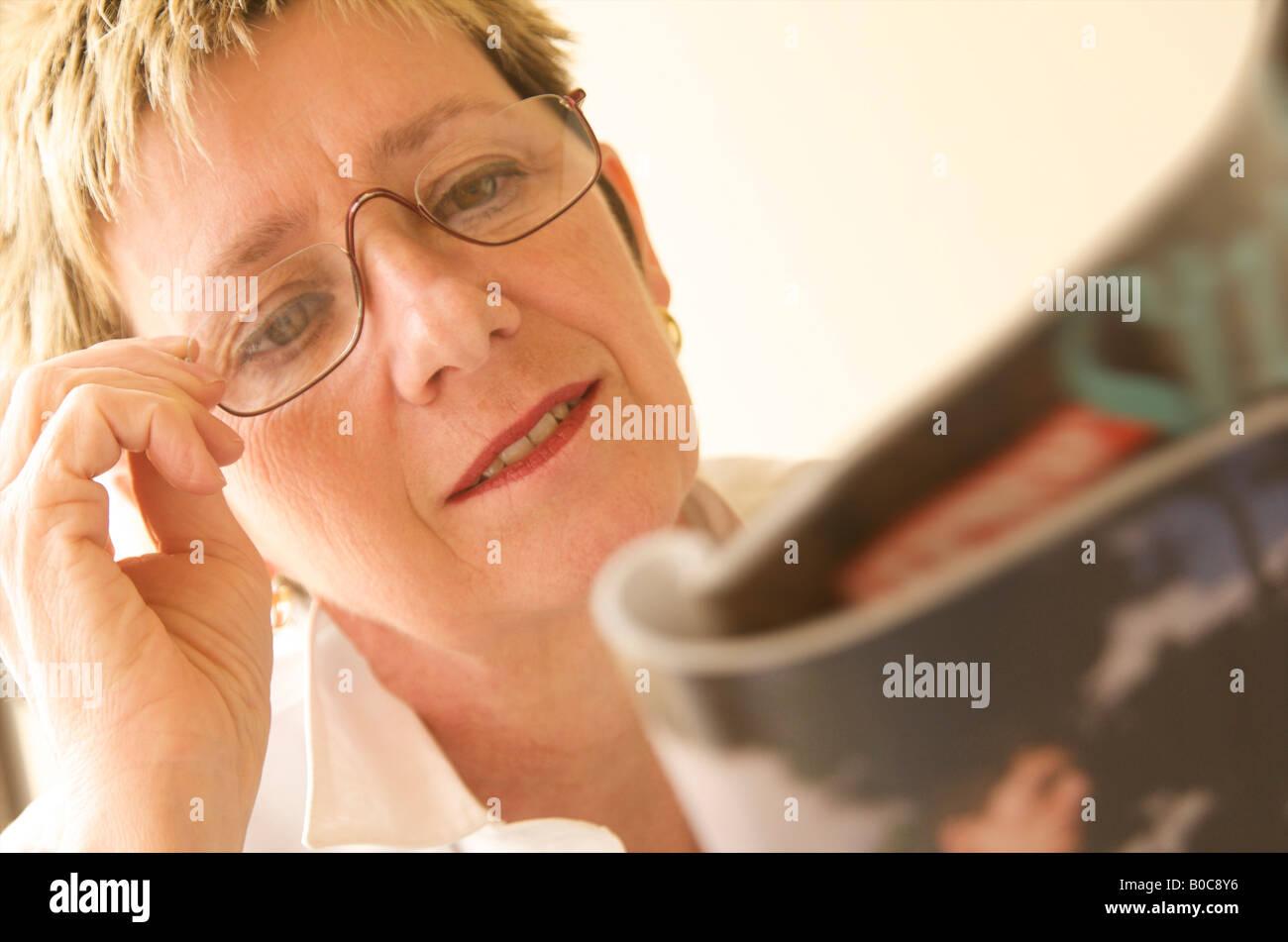 La fin de la maturité, femme d'âge moyen d'essayer de lire un magazine avec une mauvaise vision Photo Stock