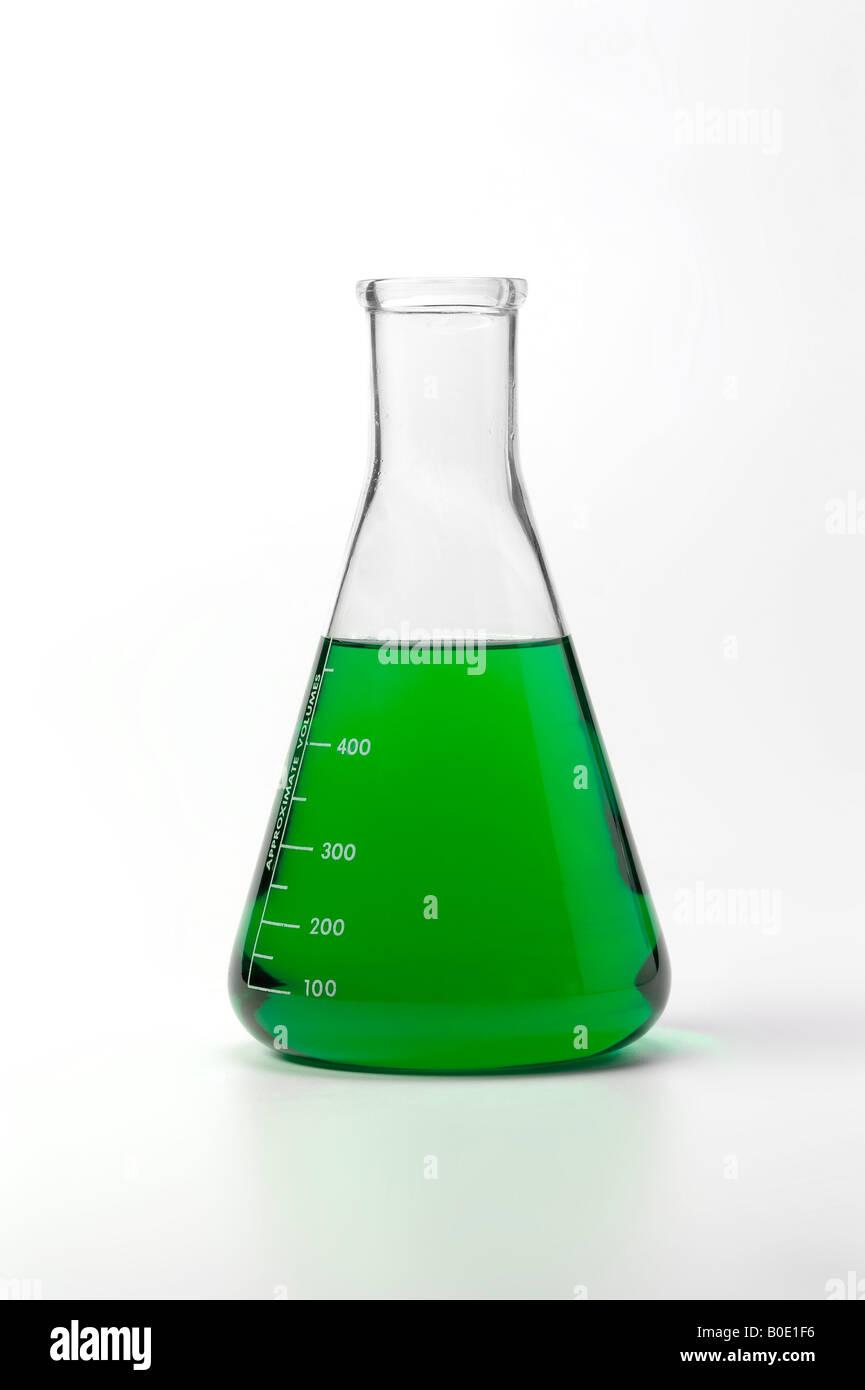 Bol avec des produits chimiques liquides colorés en vert sur fond blanc Photo Stock