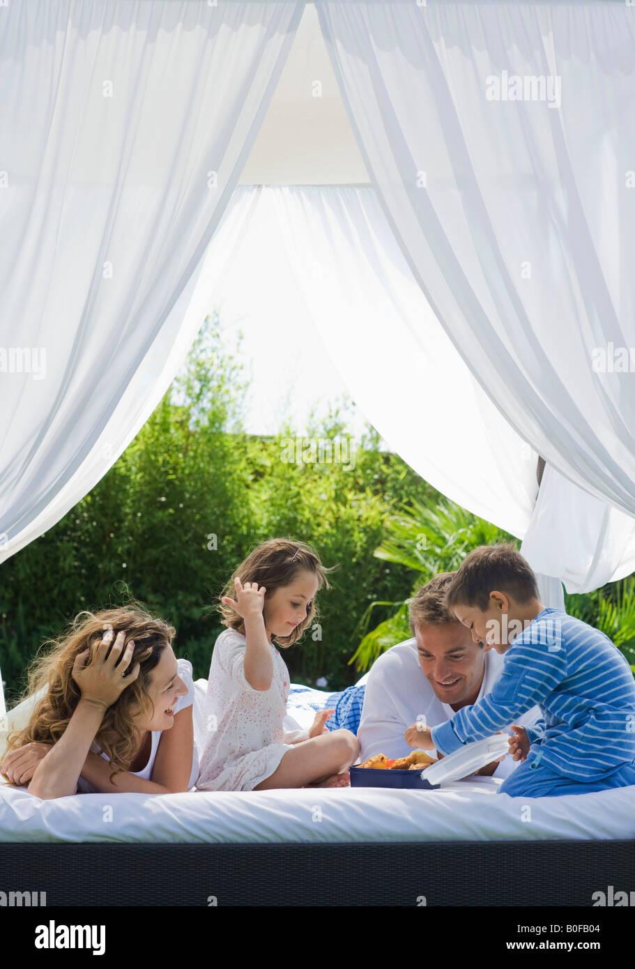 Prendre le petit déjeuner sur la famille lit dans un jardin Photo Stock