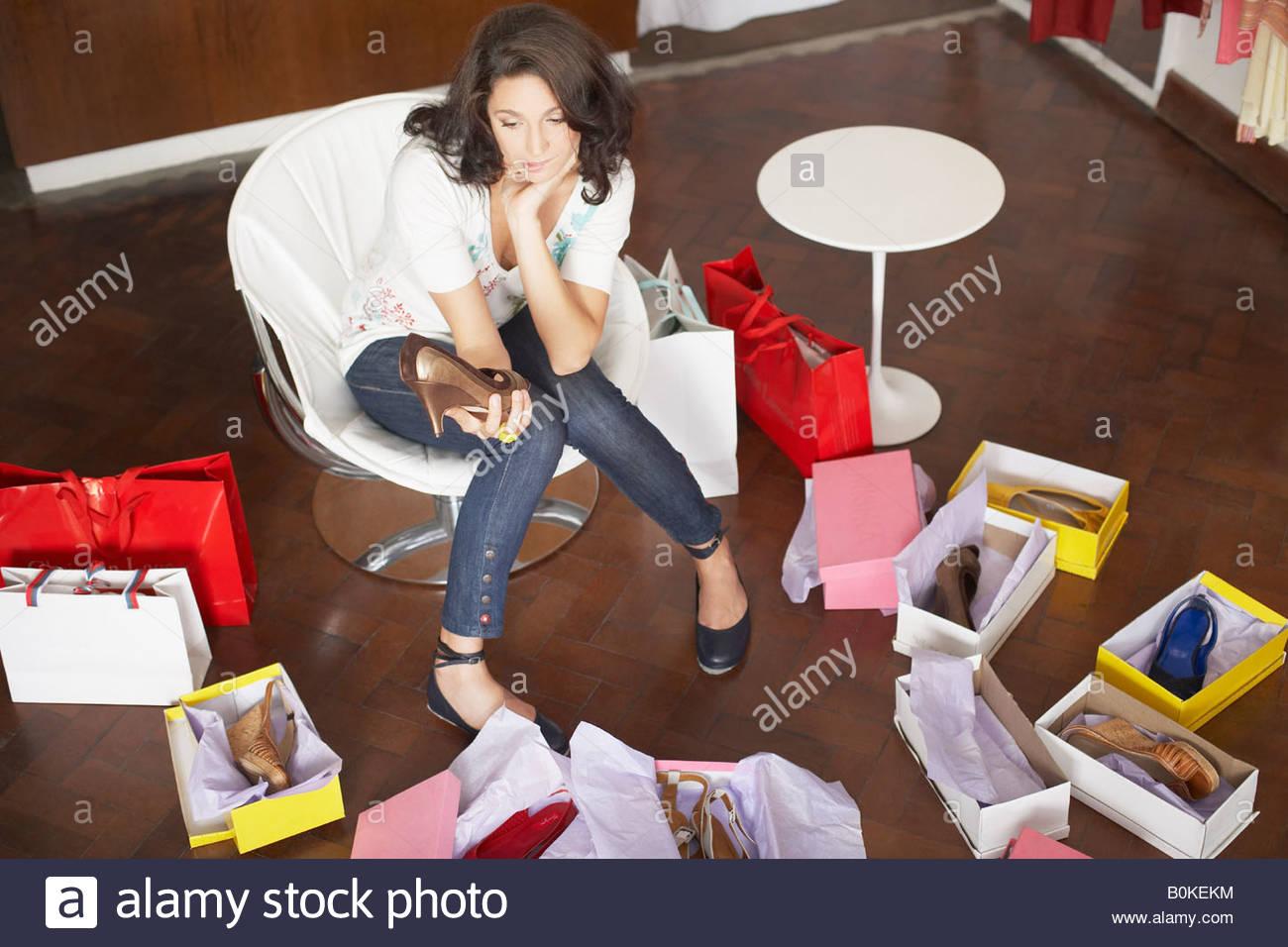 Femme dans magasin à essayer sur les chaussures Photo Stock