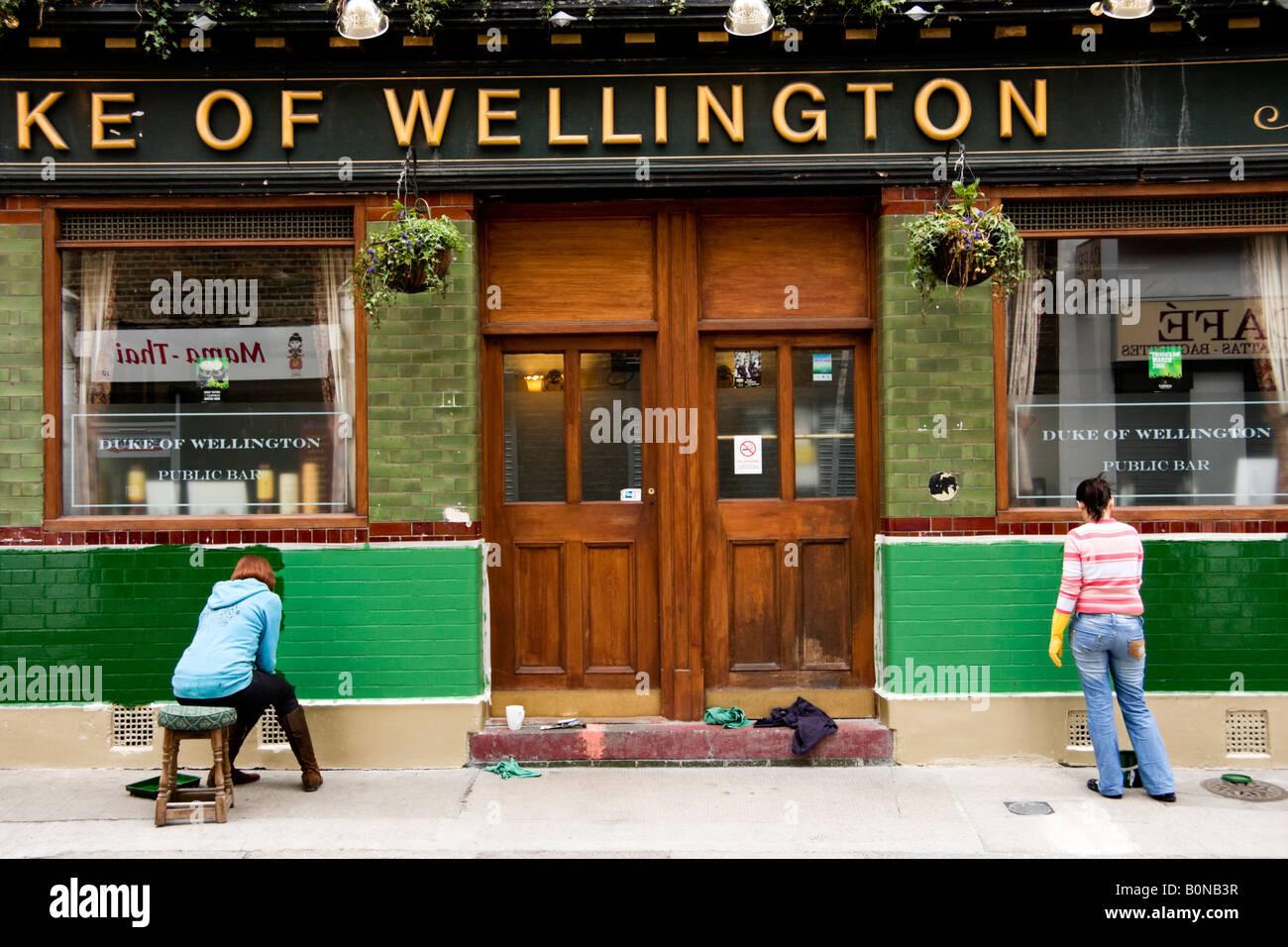 Deux femmes peinture exterieure de public house dans la région de East End de Londres Angleterre Photo Stock