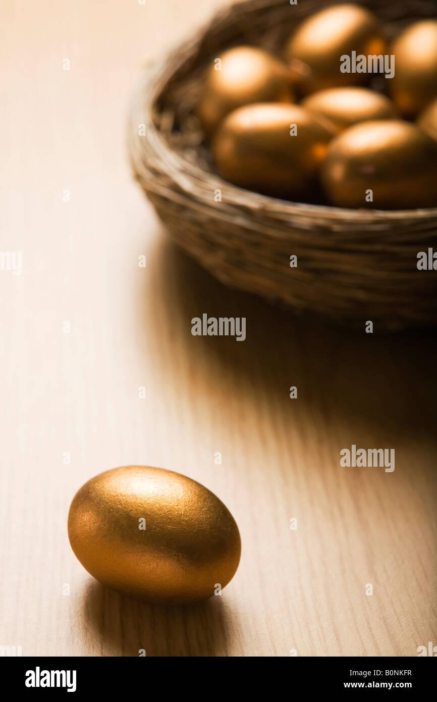 Nid d'Œufs d'or avec seul oeuf en premier plan Photo Stock