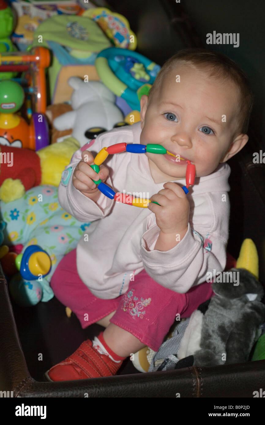 d35666dc4686e Un bébé de 9 mois fille avec anneau de dentition colorée dans sa bouche à  l intérieur de jouets à la maison