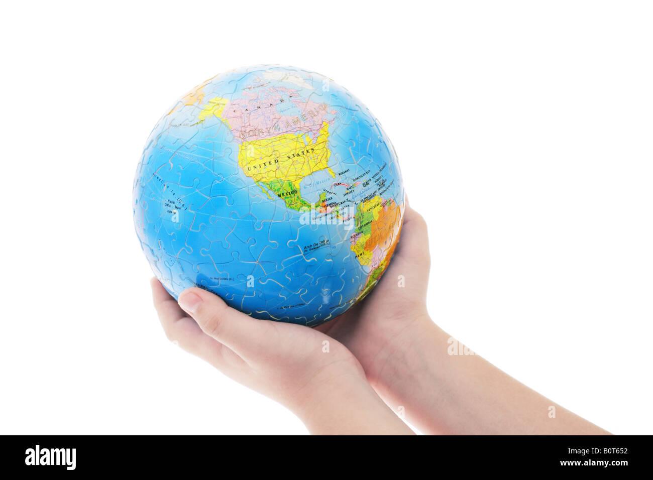 Jeune garçon s hand holding globe puzzle terminé sur fond blanc Photo Stock