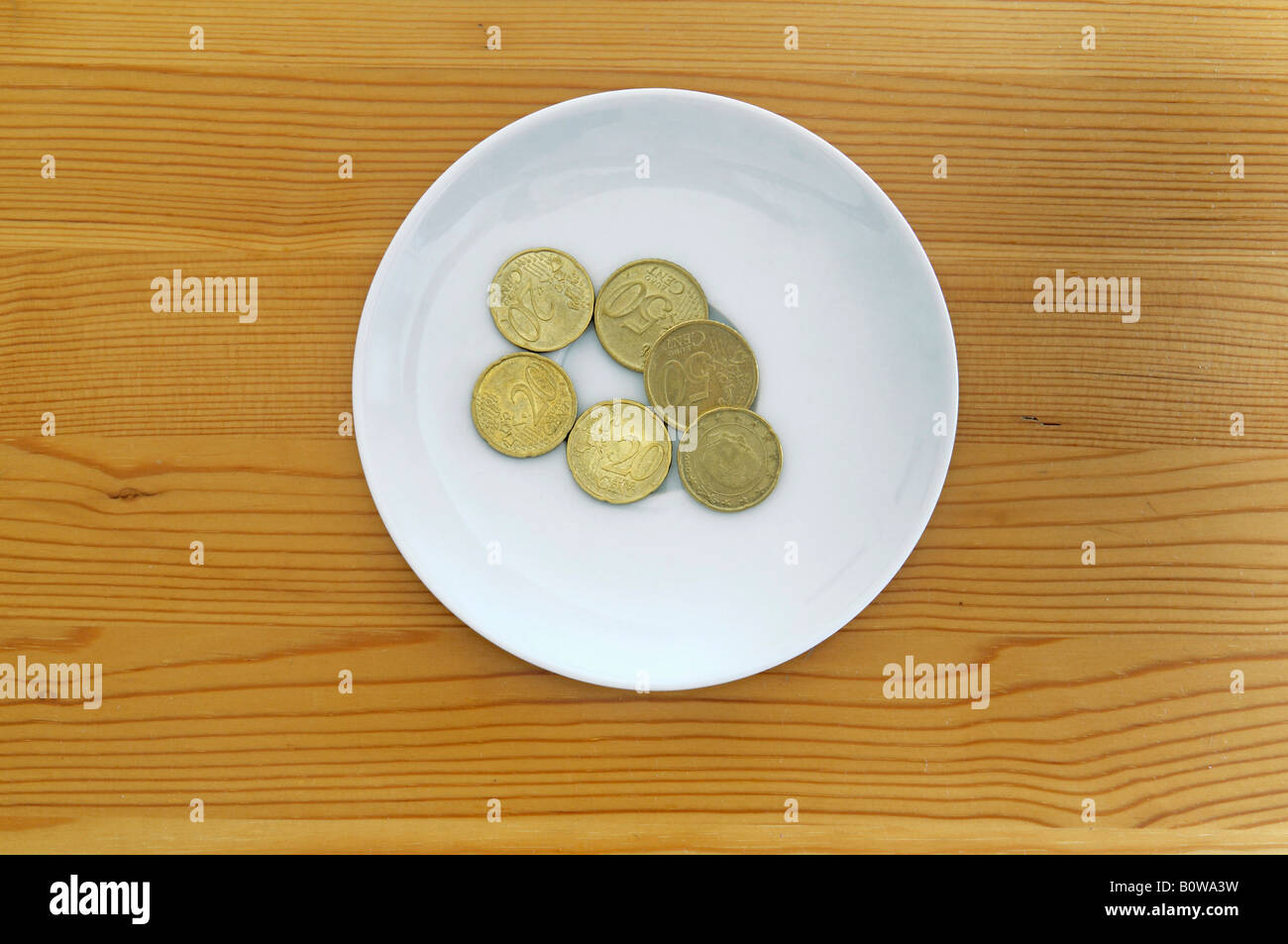 Les pièces en euros sur une assiette blanche sur une table en bois, le paiement pour l'utilisation de toilettes Banque D'Images