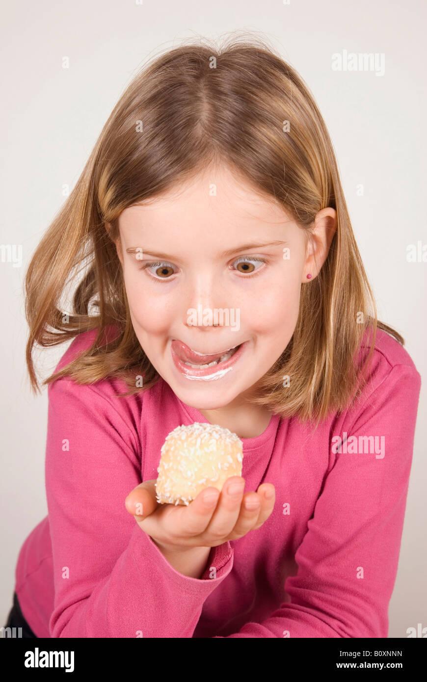 Girl (6-7) à la recherche de chocolat à la guimauve, dupant sur Photo Stock