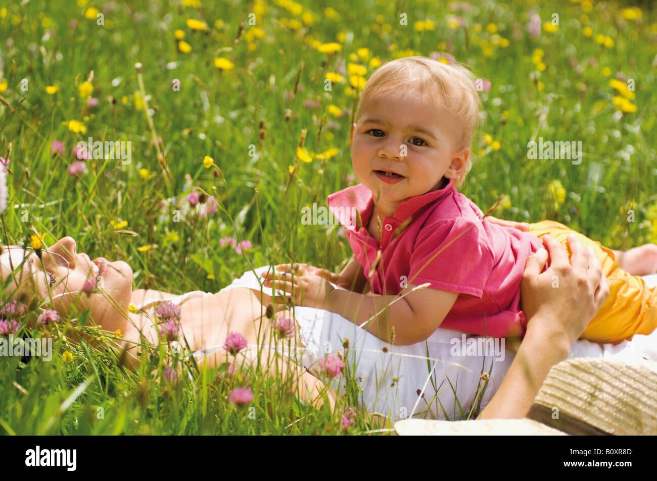 Mère avec bébé gril (2-3) dans le pré, portrait Photo Stock