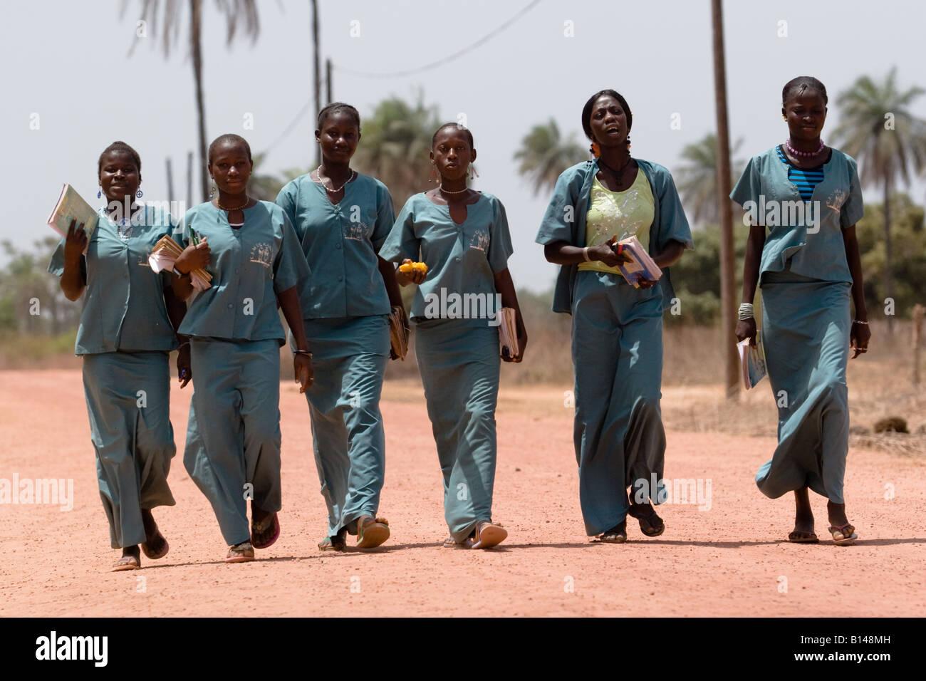 Un groupe d'étudiants en uniforme scolaire revenir à pied de l'école près du village Photo Stock
