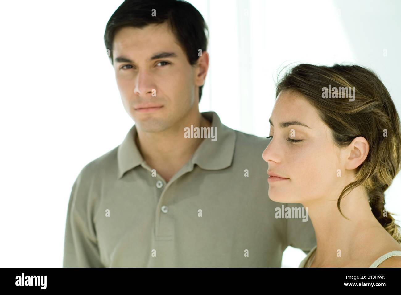 Jeune couple, man looking at camera, woman looking away Banque D'Images