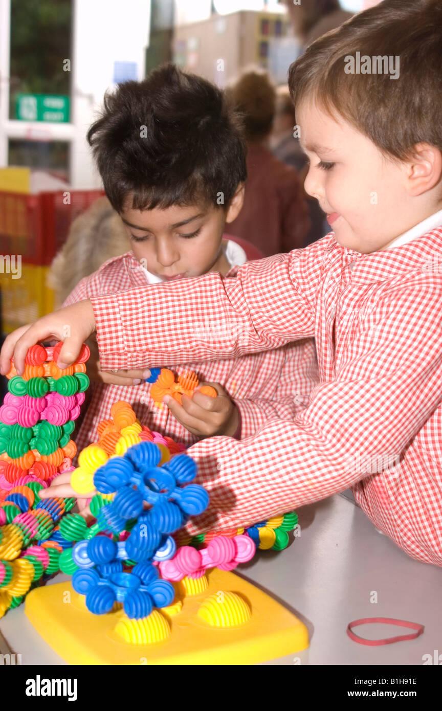 Jeune écolier jouant avec un jouet de construction Photo Stock
