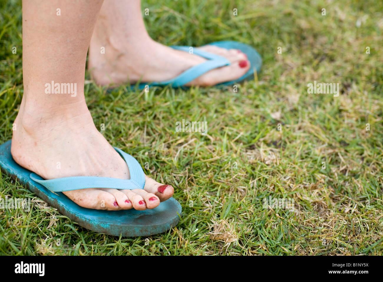 Les pieds et les orteils de la femme couverte de saleté de travaux de jardinage en sandales bleu sur pelouse avec Banque D'Images