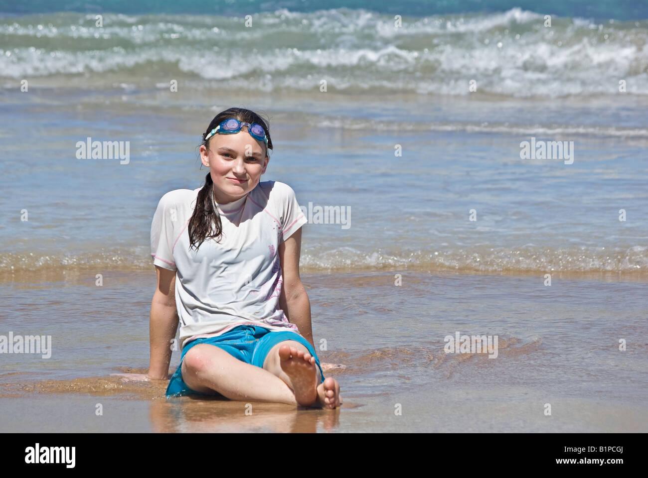 Une adolescente se trouve onn la plage Photo Stock