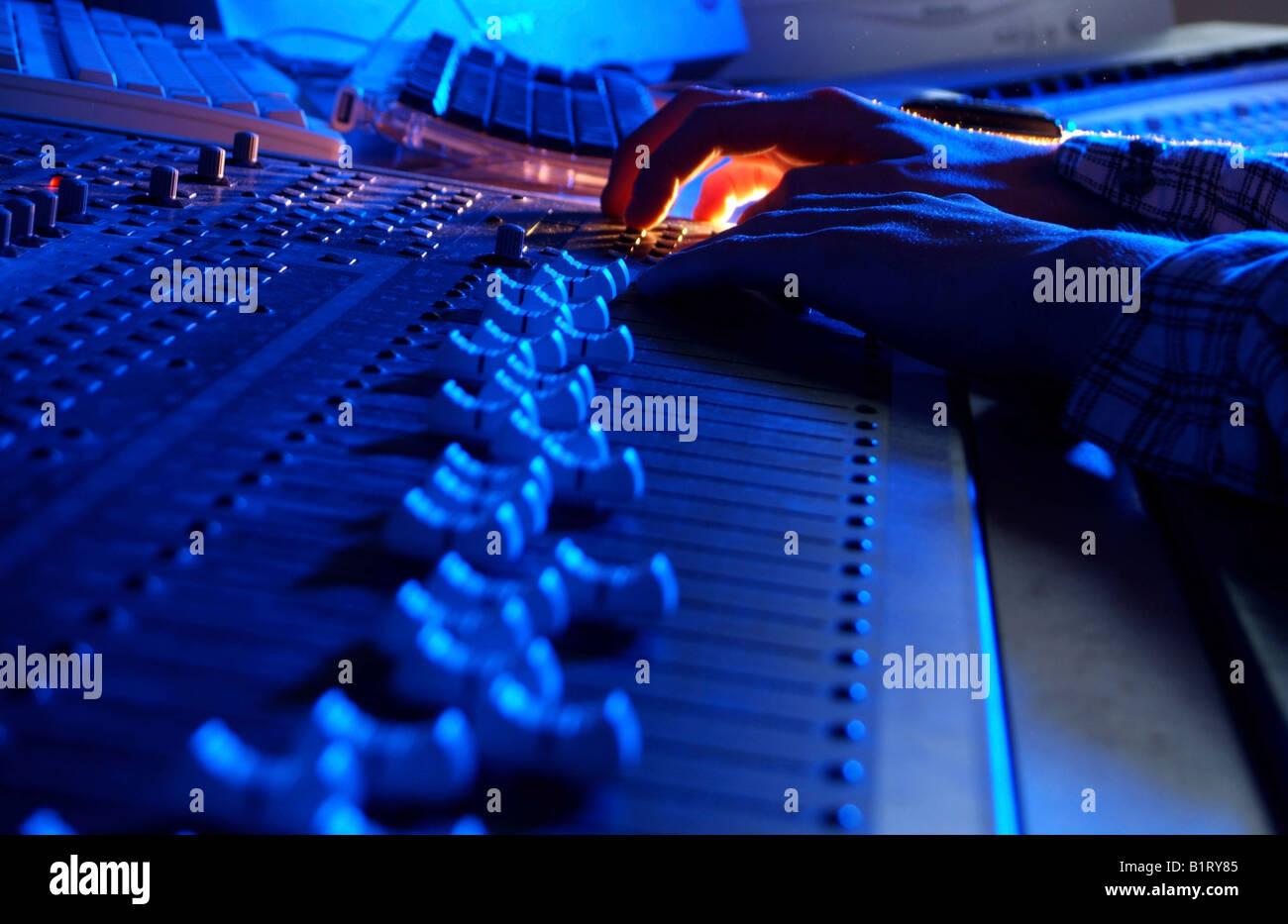 Les mains d'un ingénieur du son réglage de la réglementation d'un boîtier de mixage Photo Stock