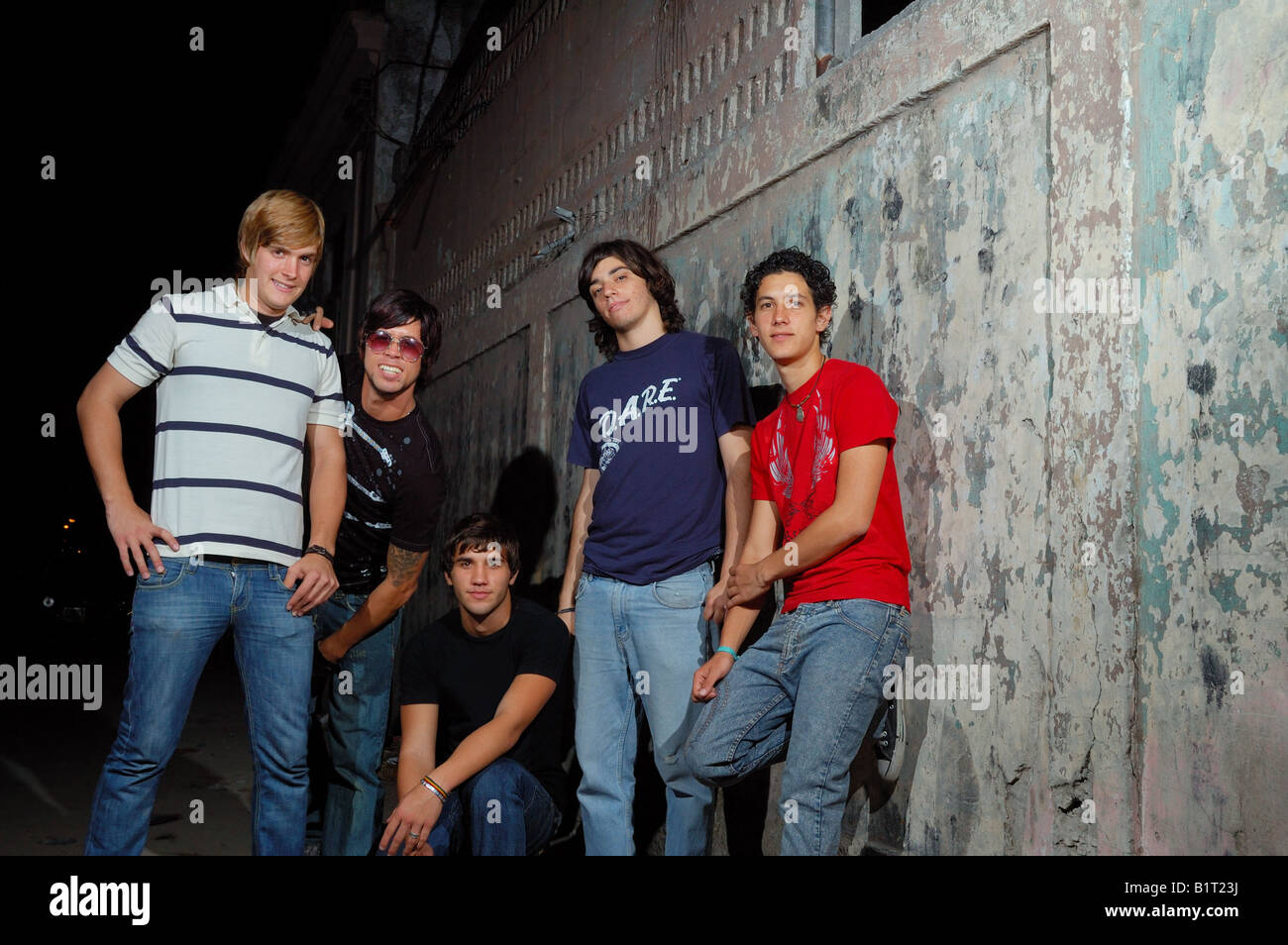 Groupe d'adolescents occasionnels contre mur grunge permanent Photo Stock