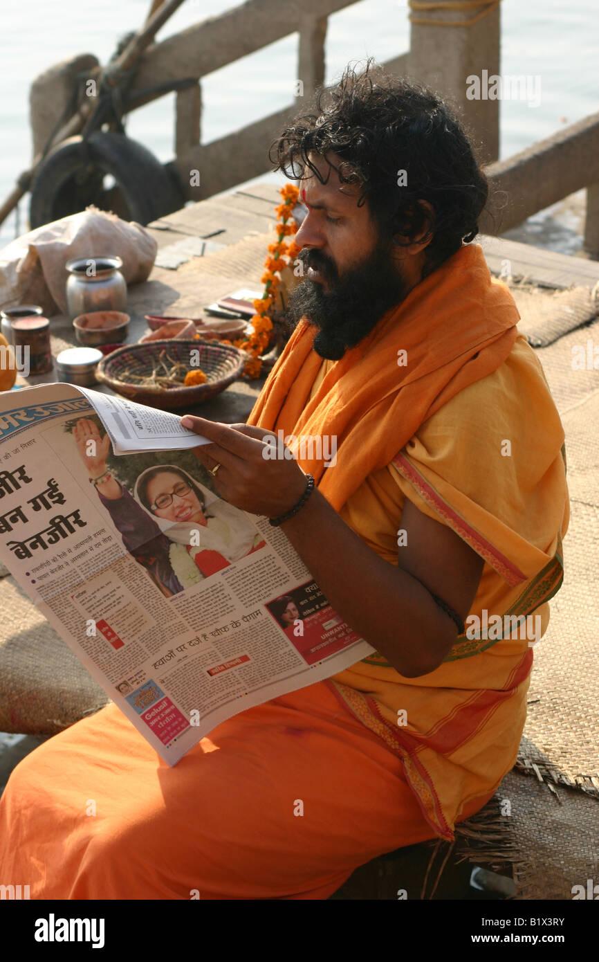 Sadhu lire le journal le matin après l'assassinat de Benazir Bhutto Photo Stock