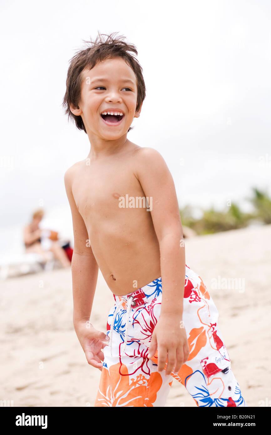 Jeune garçon (5-6 ans)rire tout en regardant ailleurs. Photo Stock