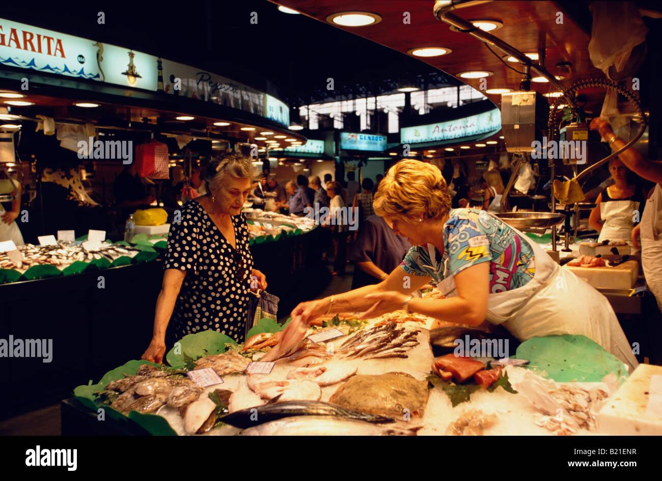 La femme est l'achat à la poissonnerie du Mercat de la Boqueria dans le Raval Ramblas de Barcelone Catalogne Espagne Banque D'Images