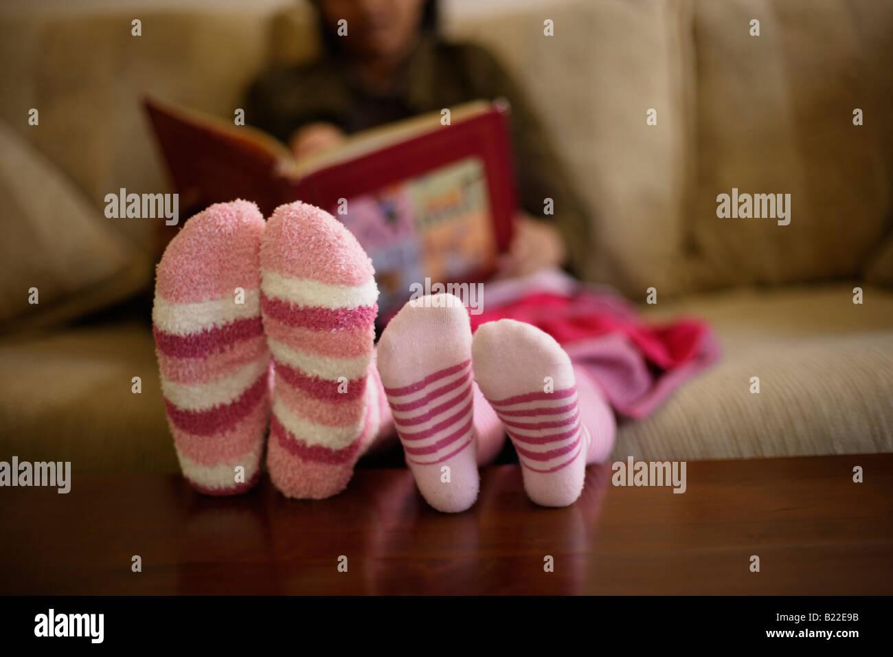 Mère indienne 30s et mixed race 4 fille lire un livre portant des chaussettes rayées rose Photo Stock