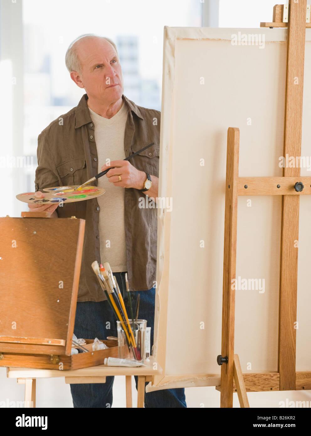 Senior man painting on easel Photo Stock