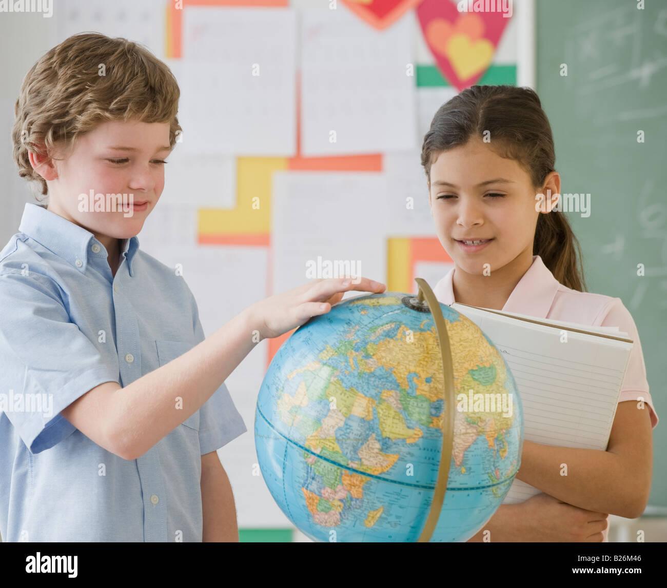 Les enfants de l'école multi-ethnique looking at globe Photo Stock