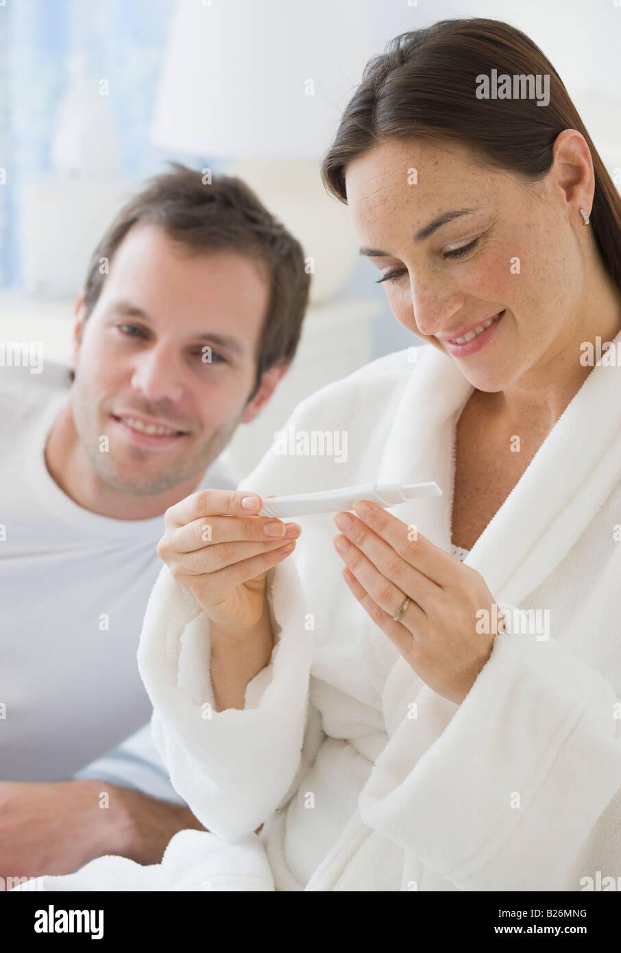Hispanic couple looking at test de grossesse Photo Stock