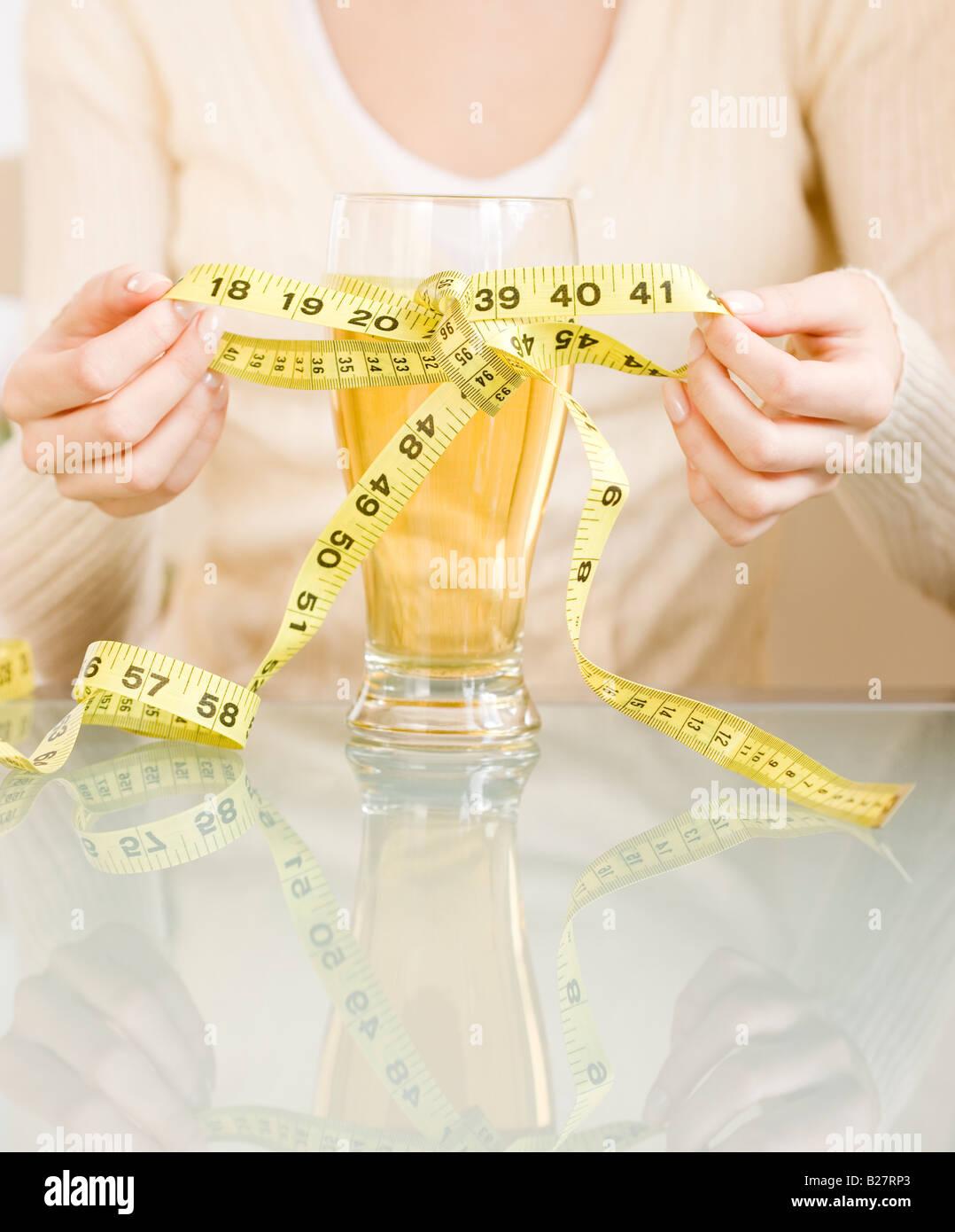 Woman ruban à mesurer de liage autour de verre de bière Photo Stock