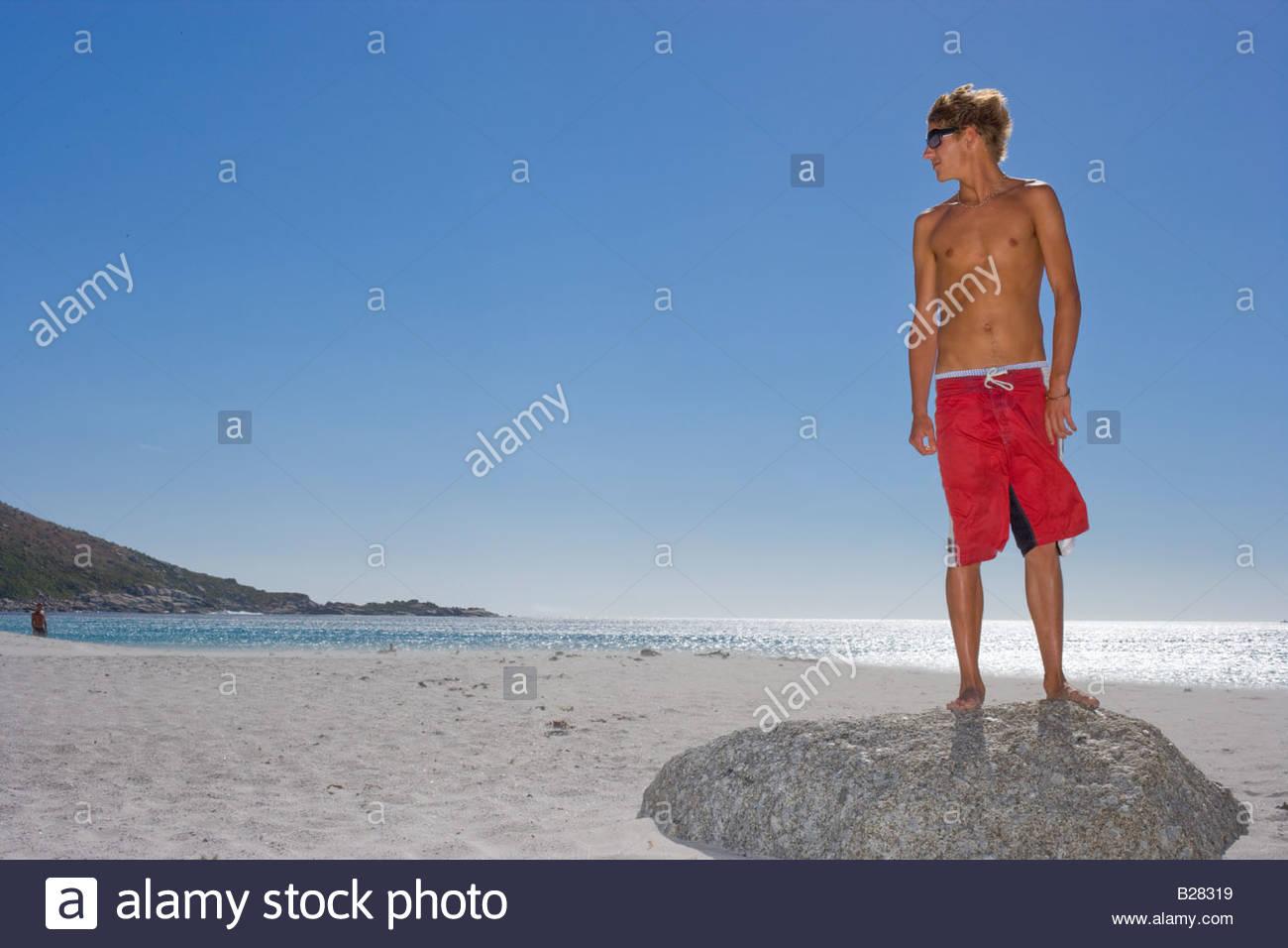 Jeune homme en maillot de bain sur rocher sur la plage, low angle view Photo Stock