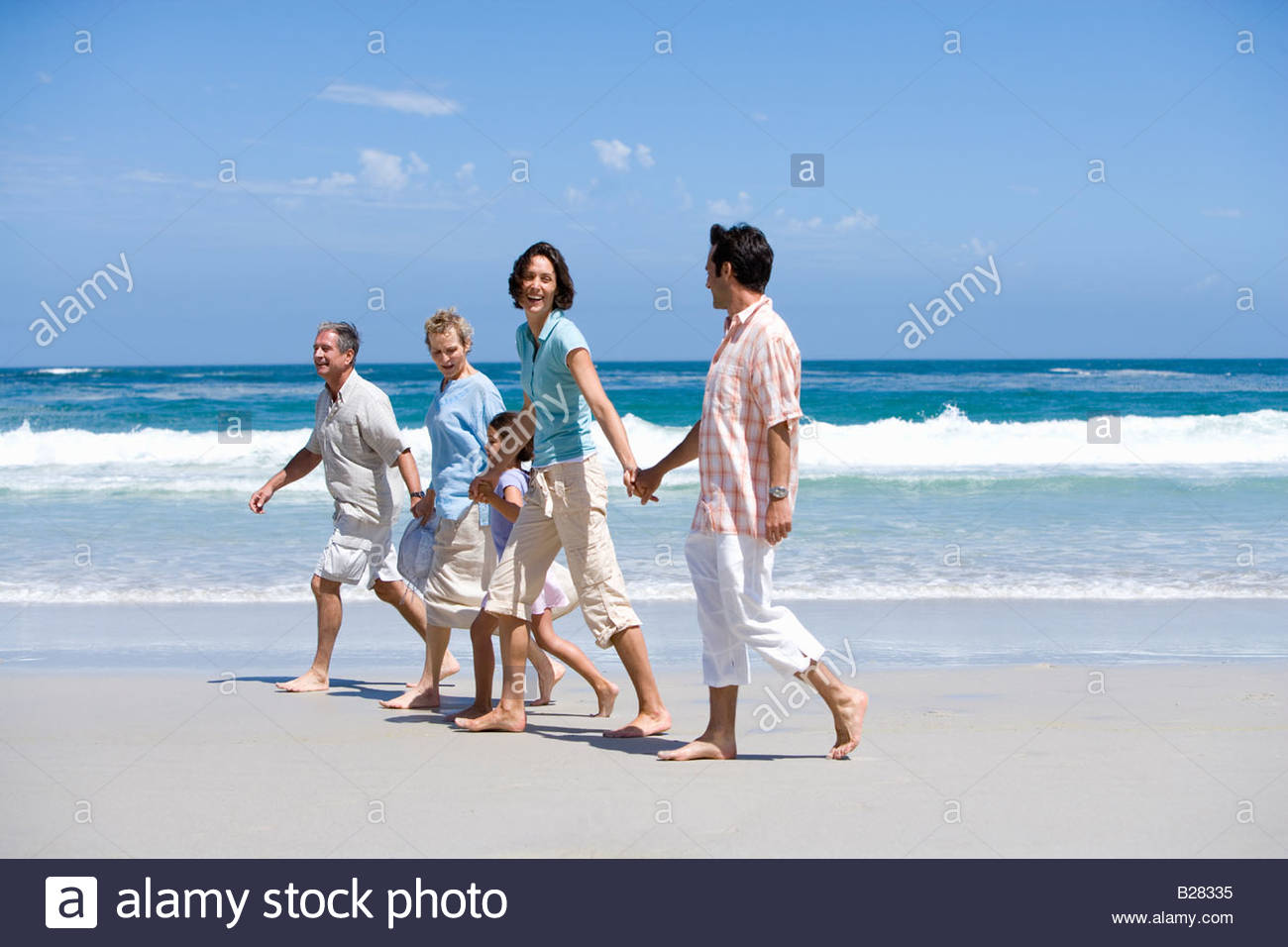 Famille de trois générations walking on beach, holding hands Photo Stock