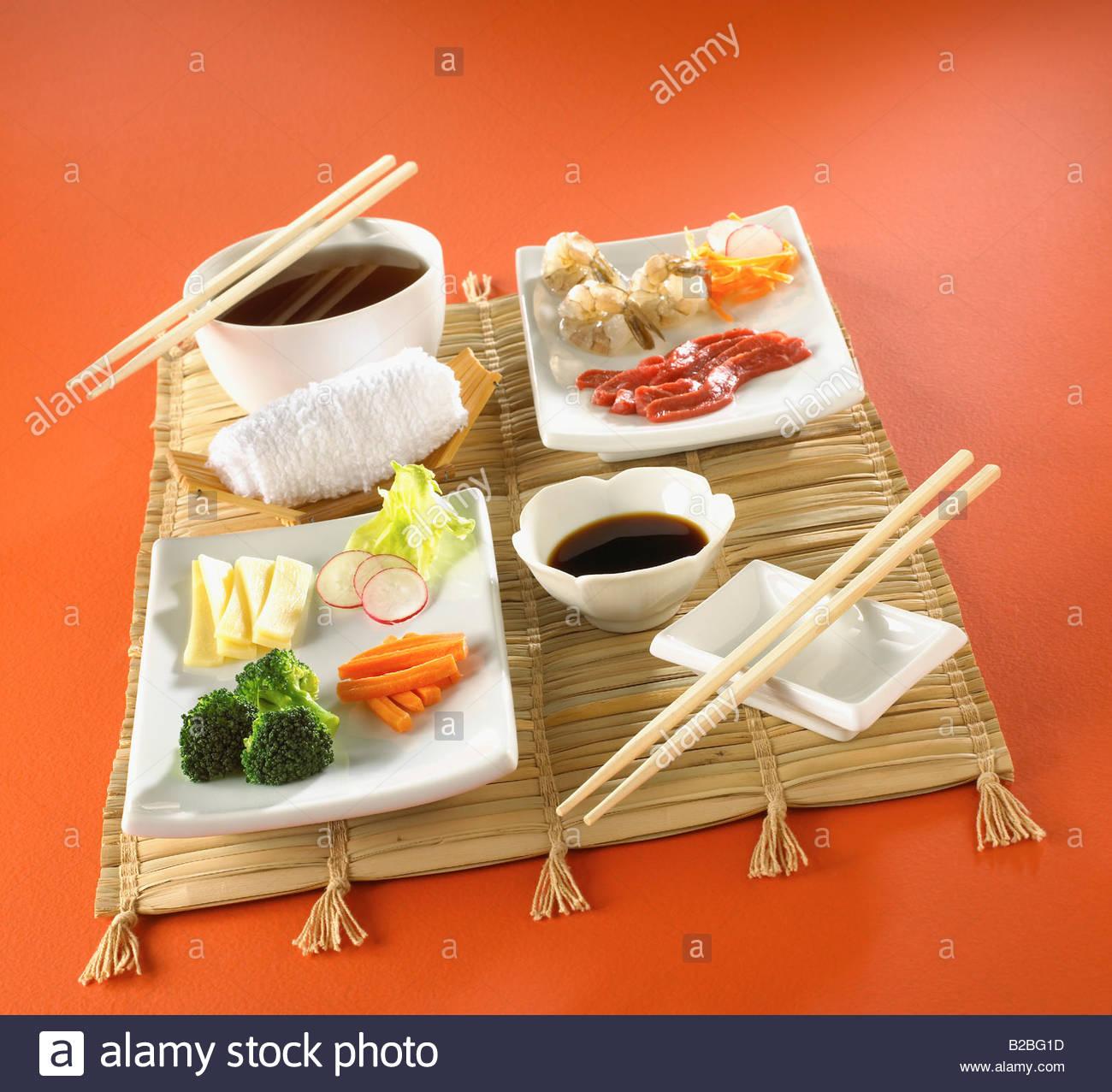 La cuisine asiatique sur tapis avec des baguettes Photo Stock