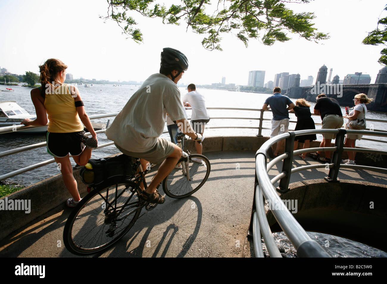 Un coureur cycliste et piétons sont vus sur une passerelle sur les bords de la Charles River à Boston Photo Stock