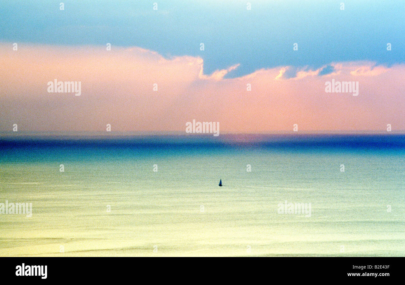 Yacht à voile à travers une ouverture dans l'océan mer calme soir lumière du matin Photo Stock