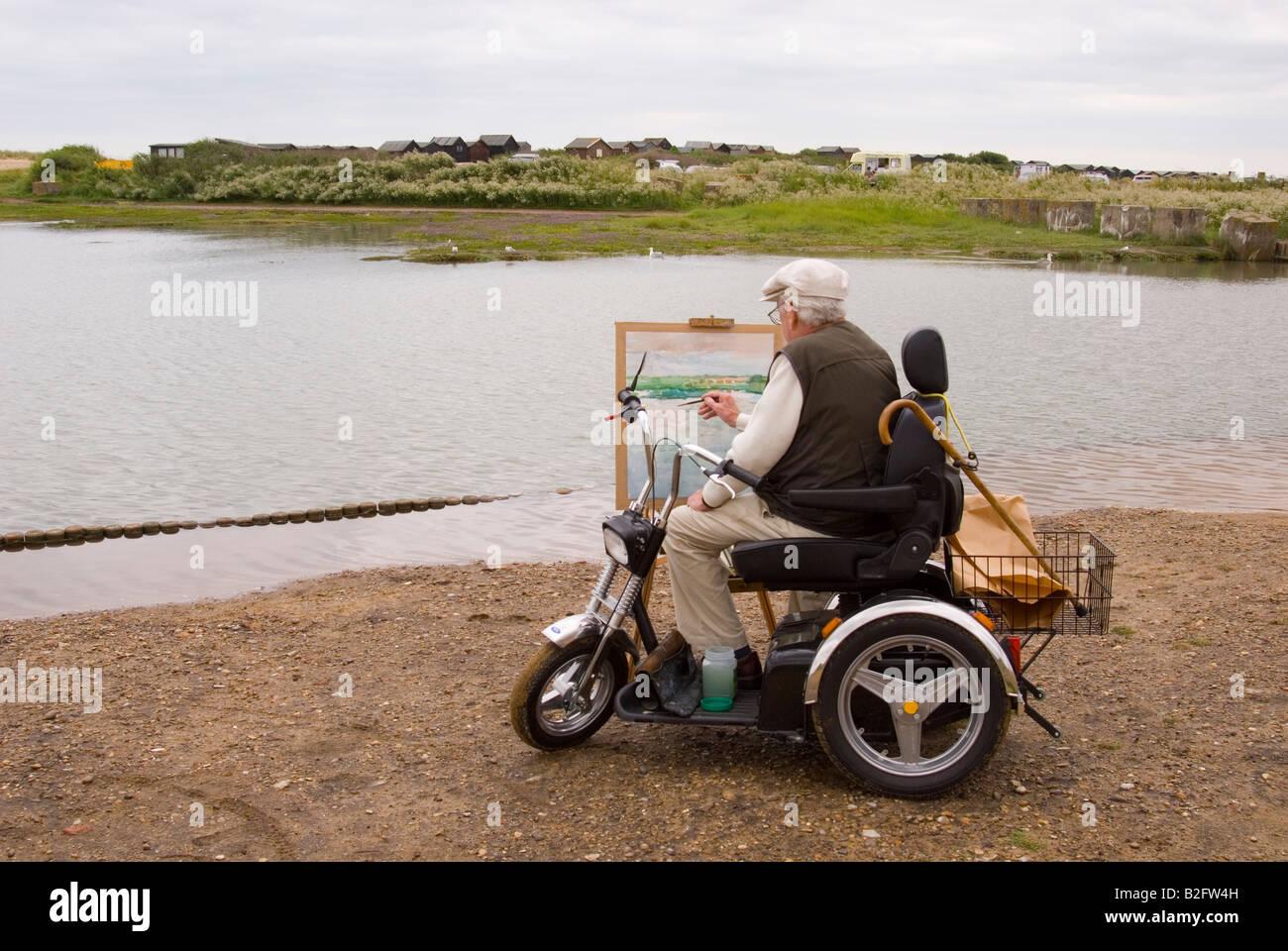 Un homme âgé sur un scooter de mobilité à peindre un paysage à Walberswick, Suffolk, UK Photo Stock