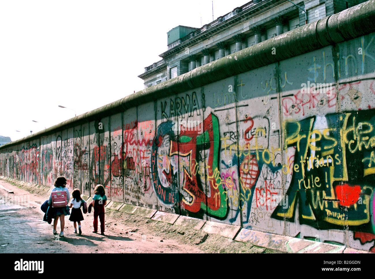 1986 les enfants à pied à la maison après l'école par le mur de Berlin Photo Stock