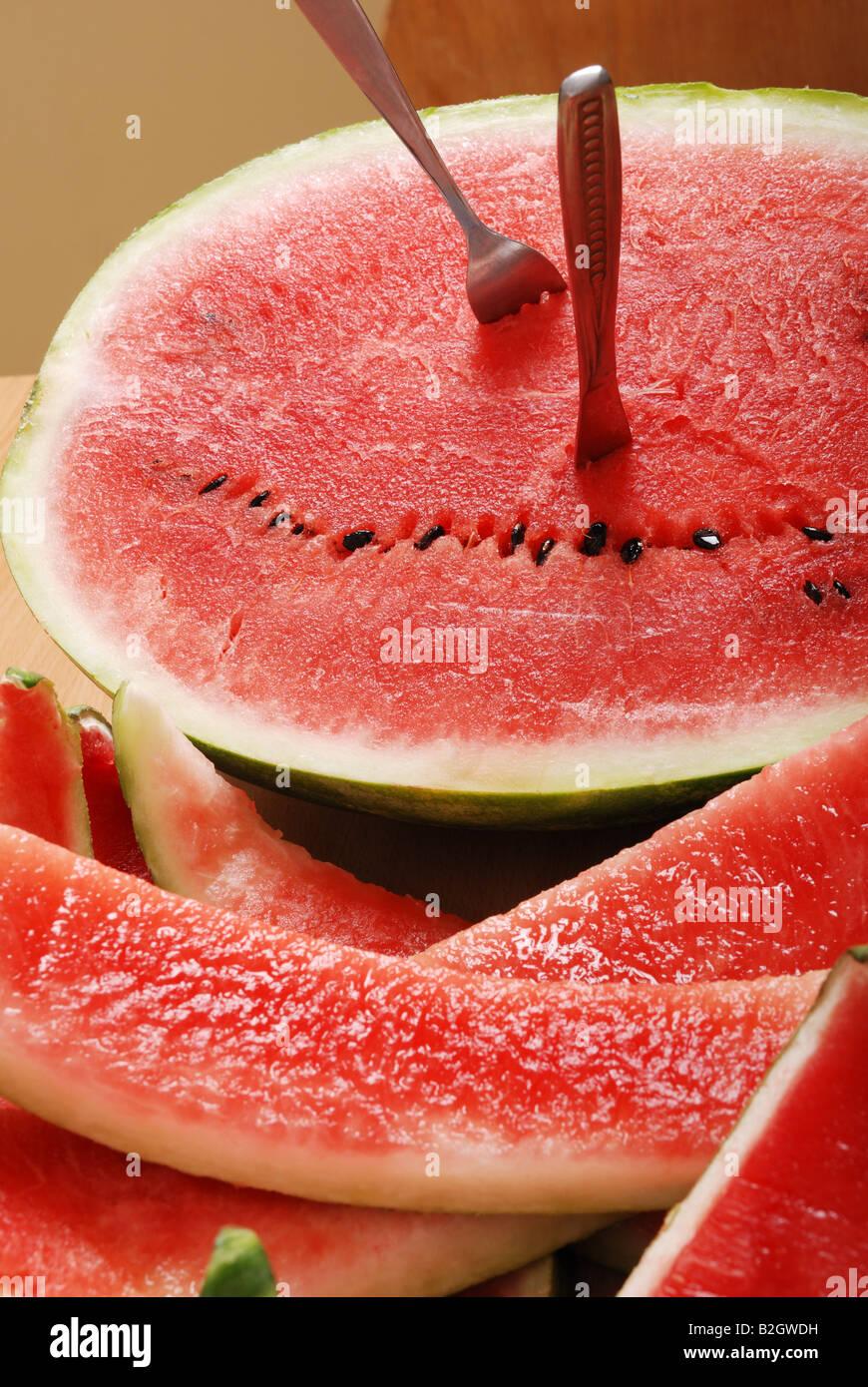 Fresh watermelon avec tranches mangé fourchette et couteau sont collée à la moitié de melon Photo Stock