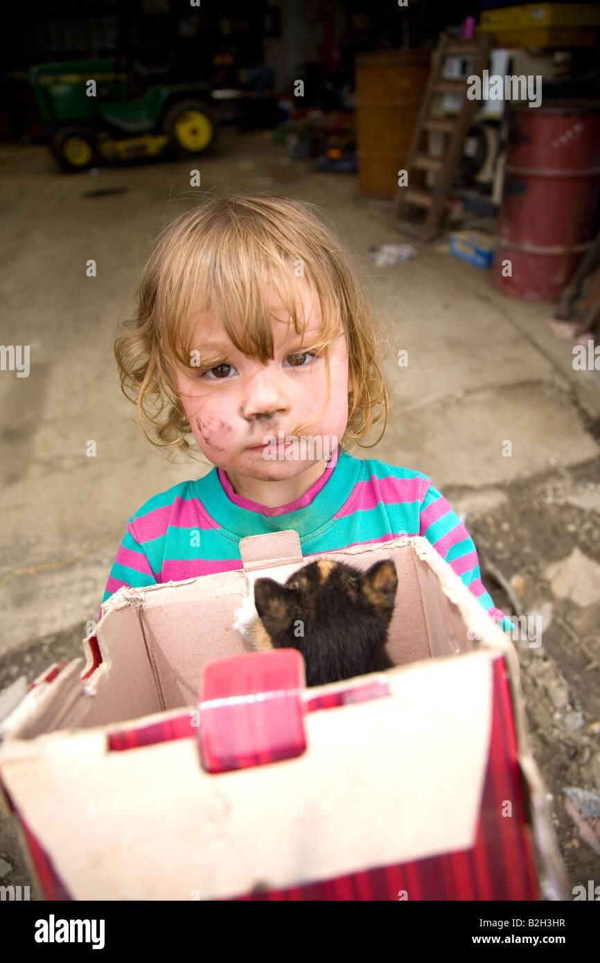 Jeune fille en milieu rural de l'Iowa, holding fort de nouveaux chatons, Iowa, États-Unis Photo Stock