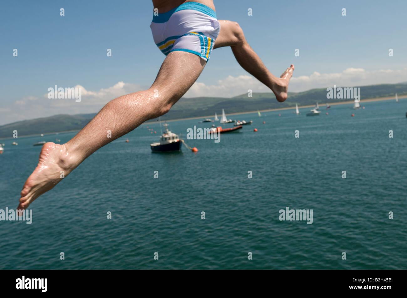 Close up des jambes d'un homme sautant au large de la jetée ou pier dans dans l'Aberdyfi Estuaire de Photo Stock