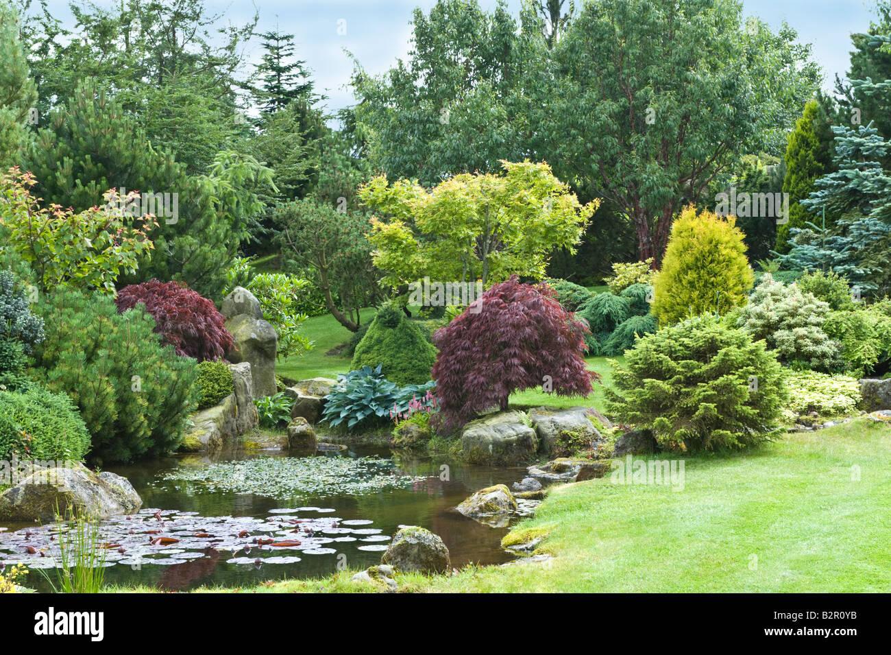 Grit-stone rocks avec étang, arbustes et arbres de jardin design par ...